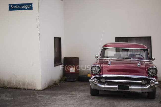 Vintage burgundy car parked outside house — Stock Photo