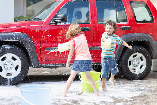 Bambini che giocano e lavano auto — Foto stock