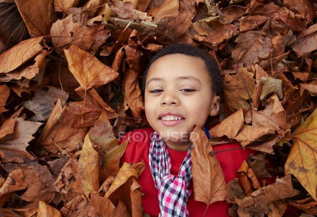 Menina jogando em folhas de outono — Fotografia de Stock
