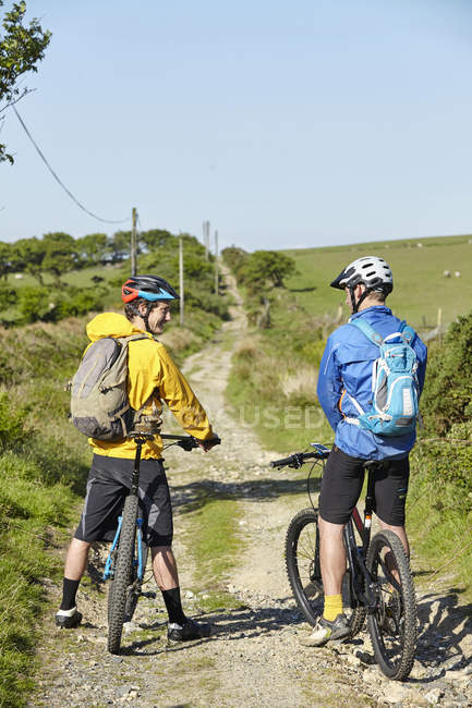Cyclists on bicycles on dirt track chatting — Stock Photo