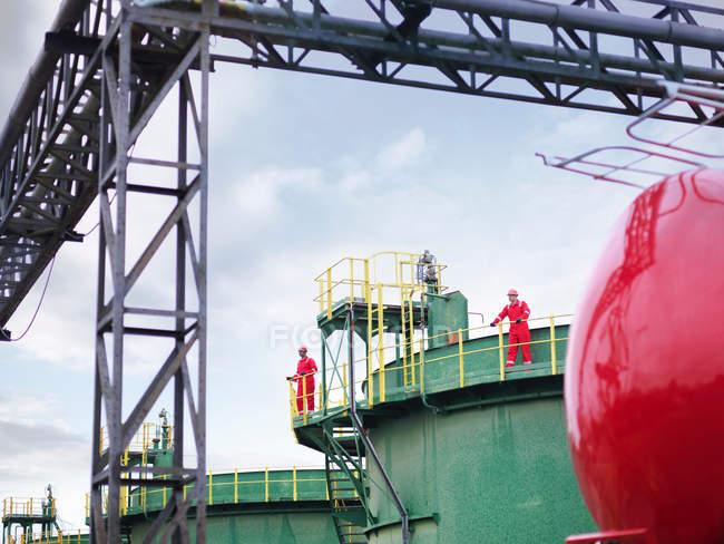 Dos trabajadores en la distancia, estaban en la pasarela de un tanque de almacenamiento de petróleo - foto de stock