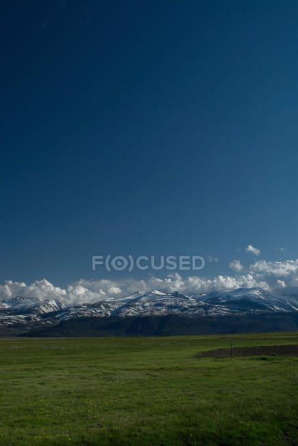 Berge mit grünen Wiese unter blauem Himmel — Stockfoto