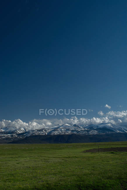 Mountains with green field under blue sky — Stock Photo