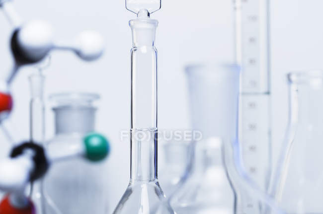 Glass bottles, volumetric flasks and chemical equipment and molecular model — Stock Photo