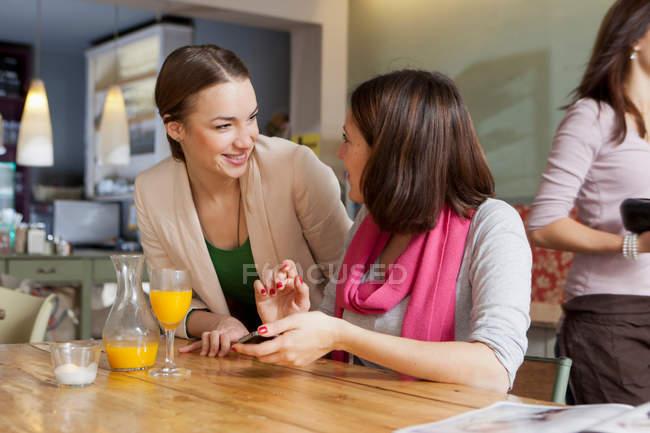 Улыбающиеся женщины разговаривают в кафе — стоковое фото