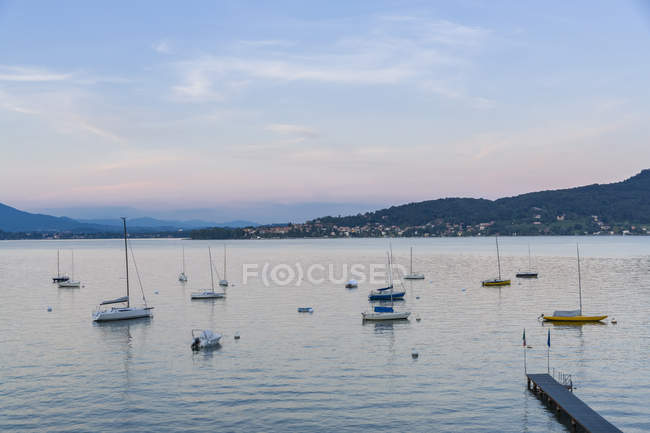 Pier and moored boats at sunset — Stock Photo