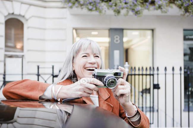 Женщина фотографирует на городской улице — стоковое фото
