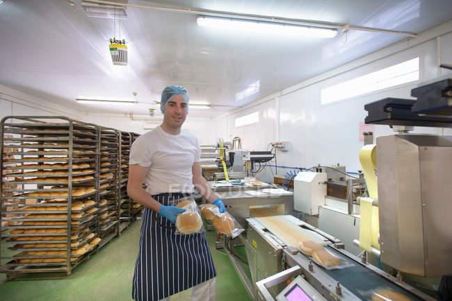 Пекарь на линии производства упаковки хлеба, портрет — стоковое фото