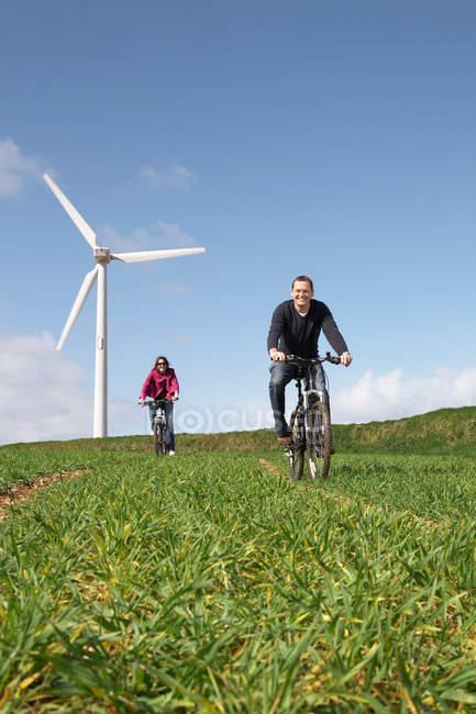 Casal andar de bicicleta em campo — Fotografia de Stock