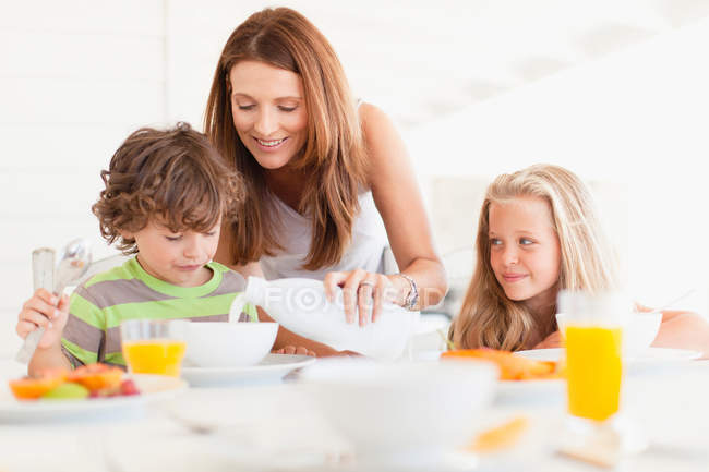 Mother pouring milk for son — Stock Photo