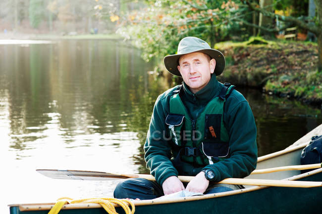 Man sitting in canoe on still lake — Stock Photo