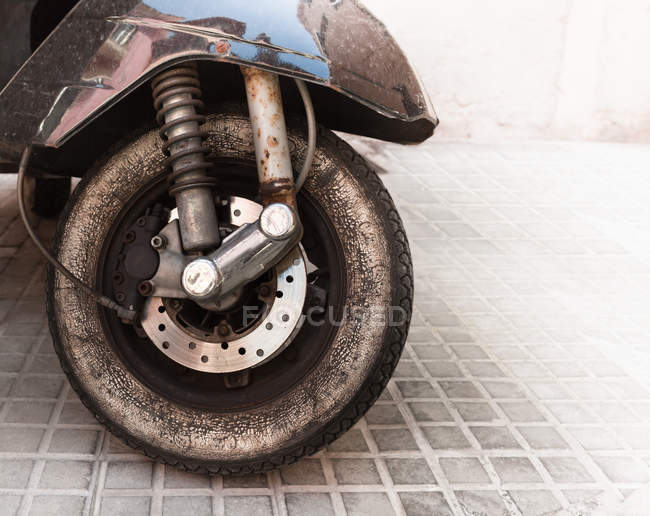 Close-up view of old dirty moped wheel with tire — Stock Photo