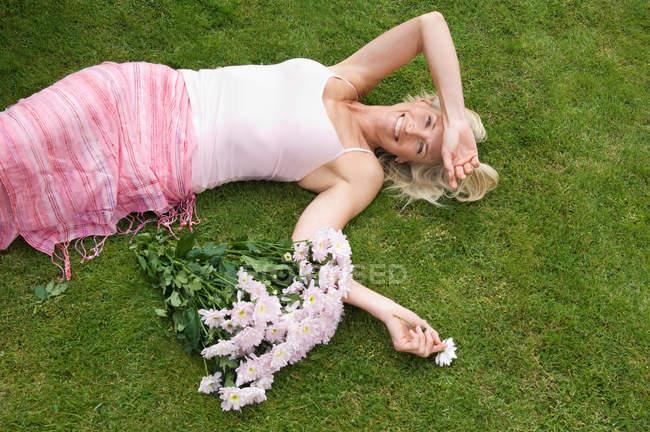 Mulher relaxada deitada na grama — Fotografia de Stock