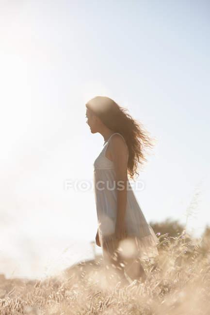 Mujer caminando en hierba alta - foto de stock