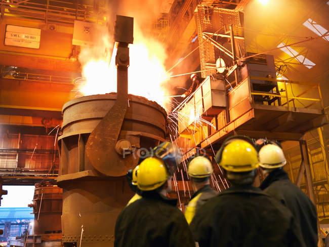 Заднього виду сталеві працівників розливу розплавлена сталь — стокове фото