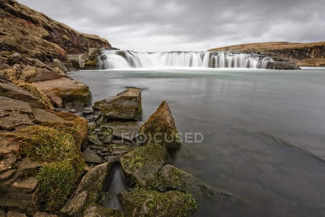 Longue exposition coup de chute d'eau qui coule et estran rocheux — Photo de stock