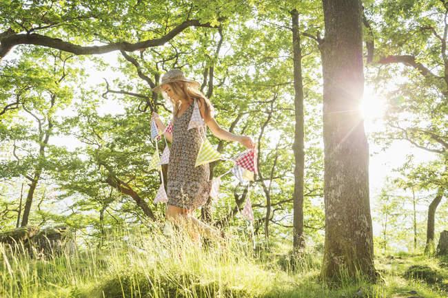 Молодая женщина, ходьба с овсянка в лесу — стоковое фото