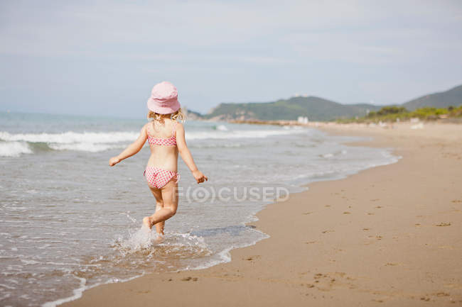 Rear view of girl walking in waves on beach — Stock Photo
