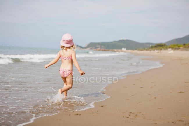 Вид сзади девушки, идущей по волнам на пляже — стоковое фото