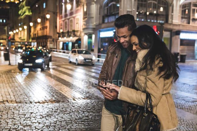 Пара в городе, ночью, глядя на смартфон, Лиссабон, Португалия — стоковое фото