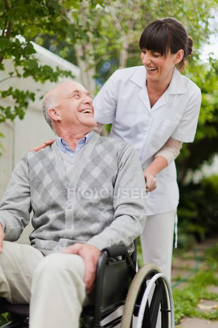 Infirmière roue patient âgé à l'extérieur — Photo de stock