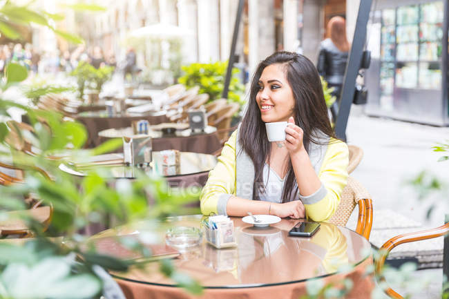 Woman at sidewalk cafe holding coffee cup looking away smiling — Stock Photo