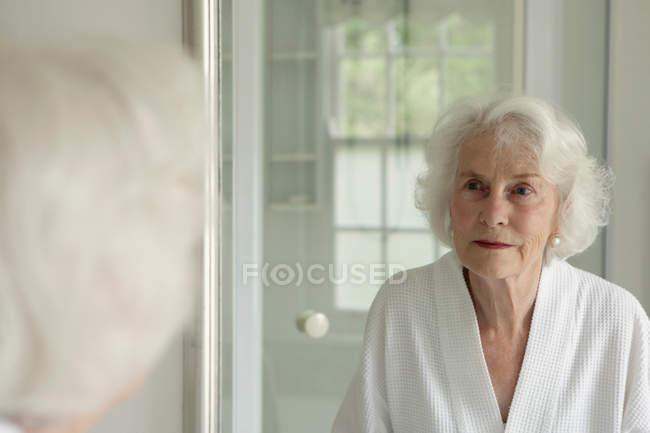 Пожилая женщина любуясь собой в зеркале — стоковое фото
