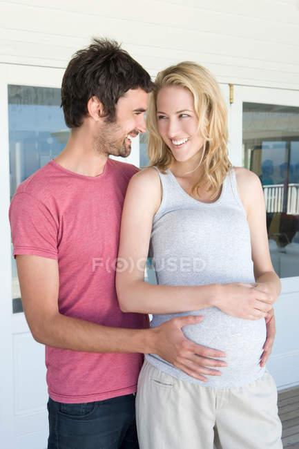 Mann hält schwangeren Mädchenbauch — Stockfoto