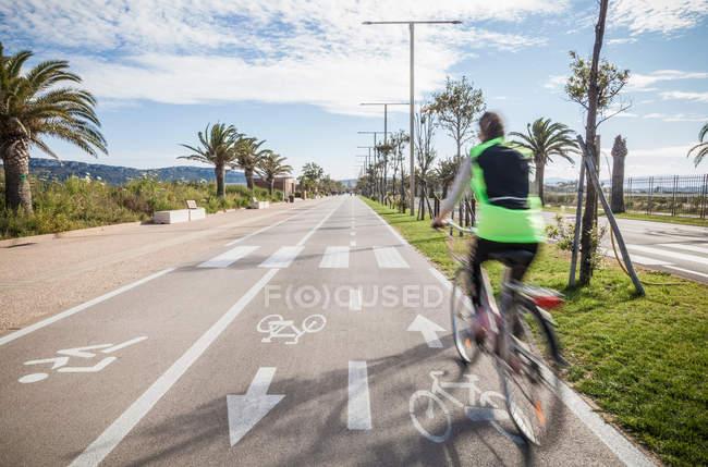 Вид сзади велосипедист носить высокий велоспорт в полосе — стоковое фото