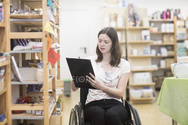 Jovem assistente de loja feminina usando estoque de cadeira de rodas na loja — Fotografia de Stock