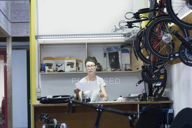 Жінка в майстерню з ремонту велосипедів позаду лічильника, дивлячись на оформлення документів — стокове фото