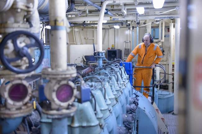Ingegnere che indossa paraorecchie che lavorano in sala macchine su rimorchiatore — Foto stock