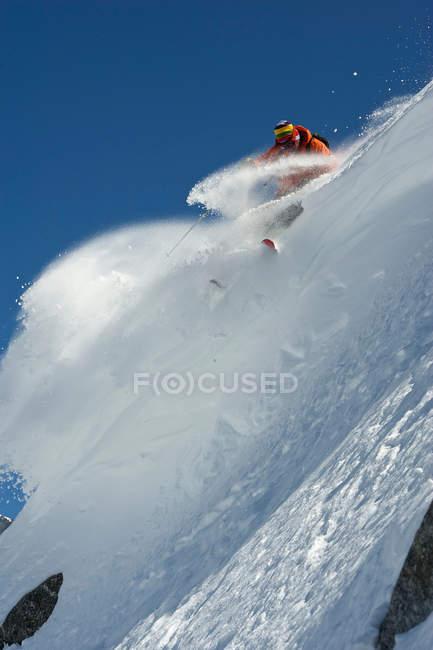 Лыжник поворачивается на крутой склоне горы — стоковое фото