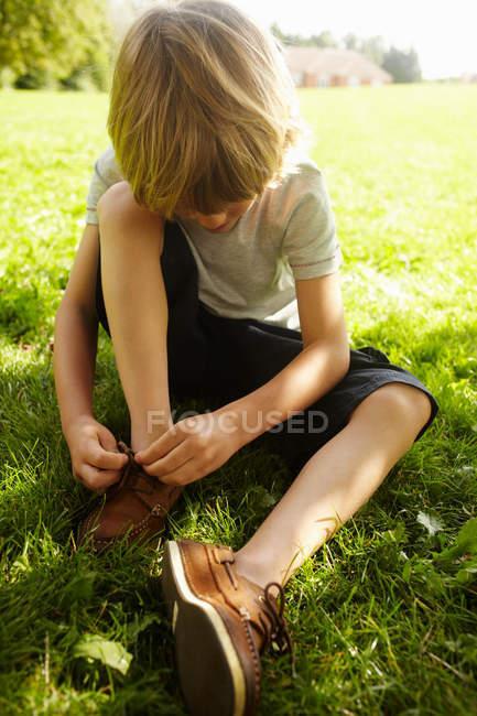 Niño atando su zapato en la hierba - foto de stock