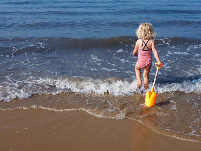 Дитина грав у воді на пляжі — стокове фото