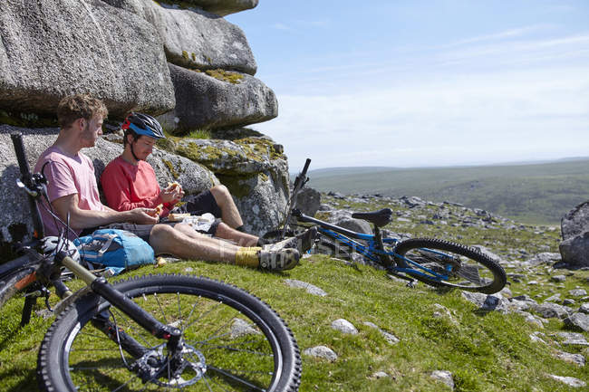 Cyclists sitting on rocky outcrop having picnic — Stock Photo