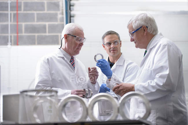 Senior engineers discussing and inspecting engineering parts that have been cleaned using ultrasonics — Stock Photo