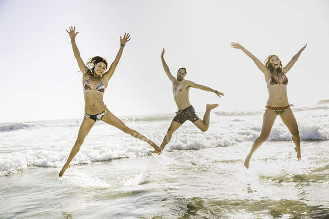 Three adult friends wearing bikini and shorts jumping  in sea, Cape Town, South Africa — Stock Photo