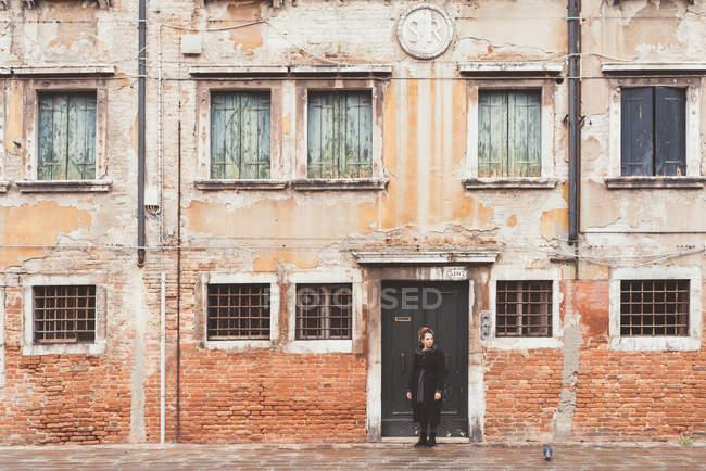 Giovane donna che guarda oltre la sua spalla dalla vecchia porta, Venezia, Italia — Foto stock