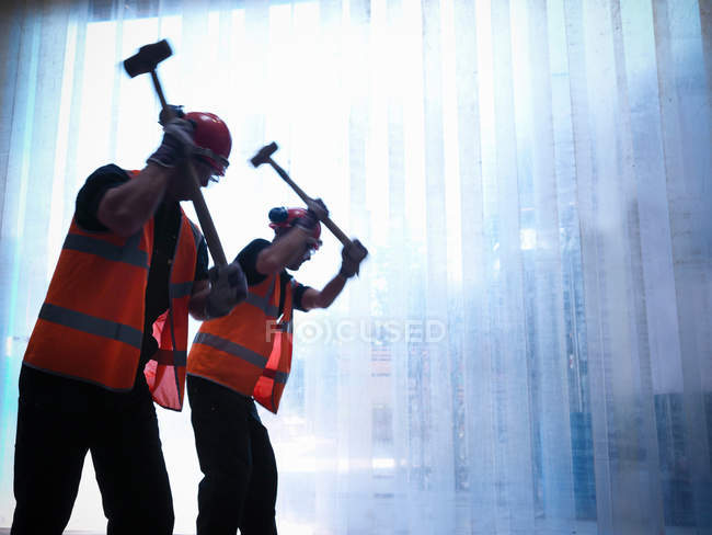 Silhouette of workers swinging hammers - foto de stock