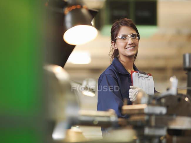 Mujer aprendiz con portapapeles en taller - foto de stock