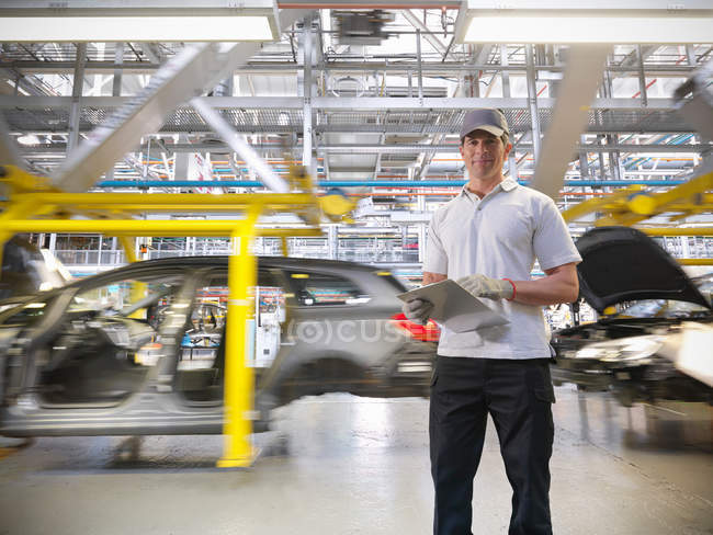 Портрет рабочего с автомобилями на производственной линии на автомобильном заводе — стоковое фото