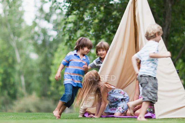 Niños jugando en tienda al aire libre - foto de stock