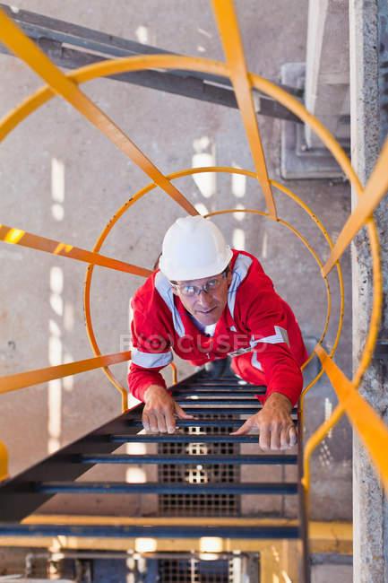 Échelle d'escalade ouvrière à la raffinerie de pétrole — Photo de stock