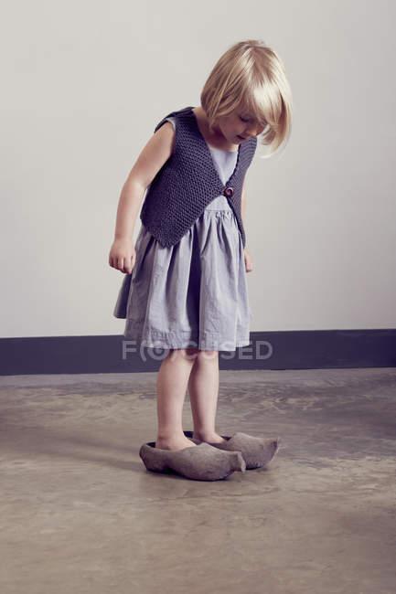 Ragazza in piedi in zoccoli di legno vintage guardando giù — Foto stock