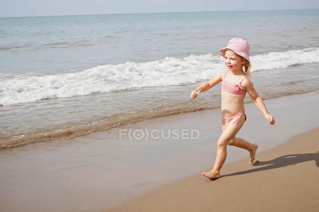 Mädchen mit Sonnenhut läuft am Strand — Stockfoto