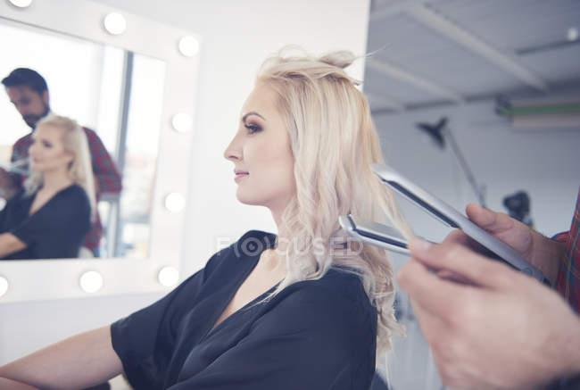Le mani di parrucchiere che tengono piastre per capelli per modello all'atto di servizio fotografico — Foto stock