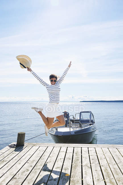 Young woman leaping mid air on pier — Stock Photo