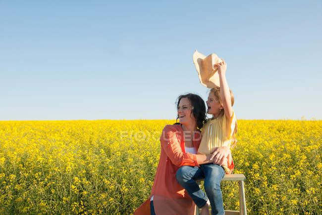 Mère et fille dans le champ de fleurs — Photo de stock