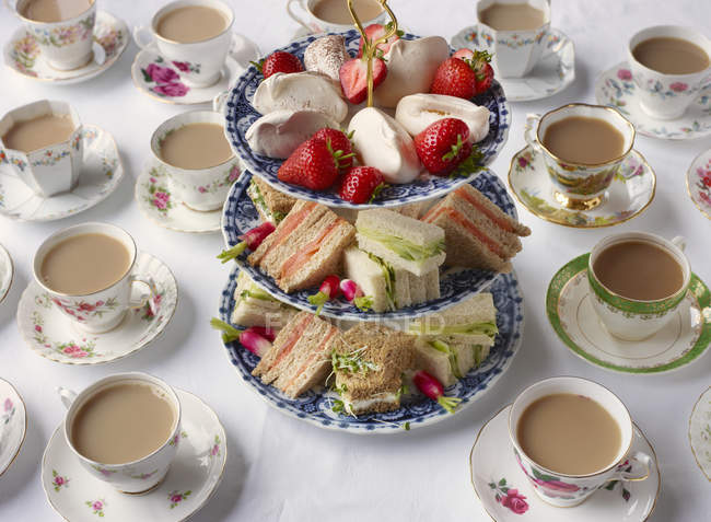Vintage tea cups and sandwiches on cakestand prepared for afternoon tea — Stock Photo